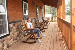 Sherie Tellinghuisen sits in one of the rockers on the porch of the Home Town Hotel in Willow Lake. Photo by Clark County Courier