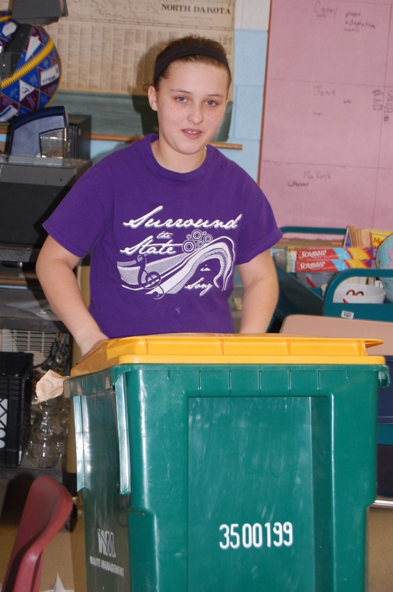 Left: Pacey Grosgebauer moves a recycling bin during recycling preparation at North Sargent school. Photo by Kirstin Kempel