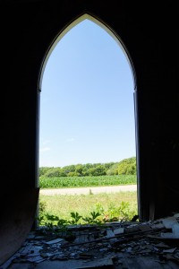 The doorway of the old church frames the farm scene across the road. Photo by Troy Larson