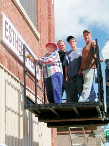 "Esther Lindgren drills the last screw in the sign ""Esther's Plaza"" while Russ Vaughn, Austin Bjugstad and Chuck Christ assist. Photo by Kulm Messenger"