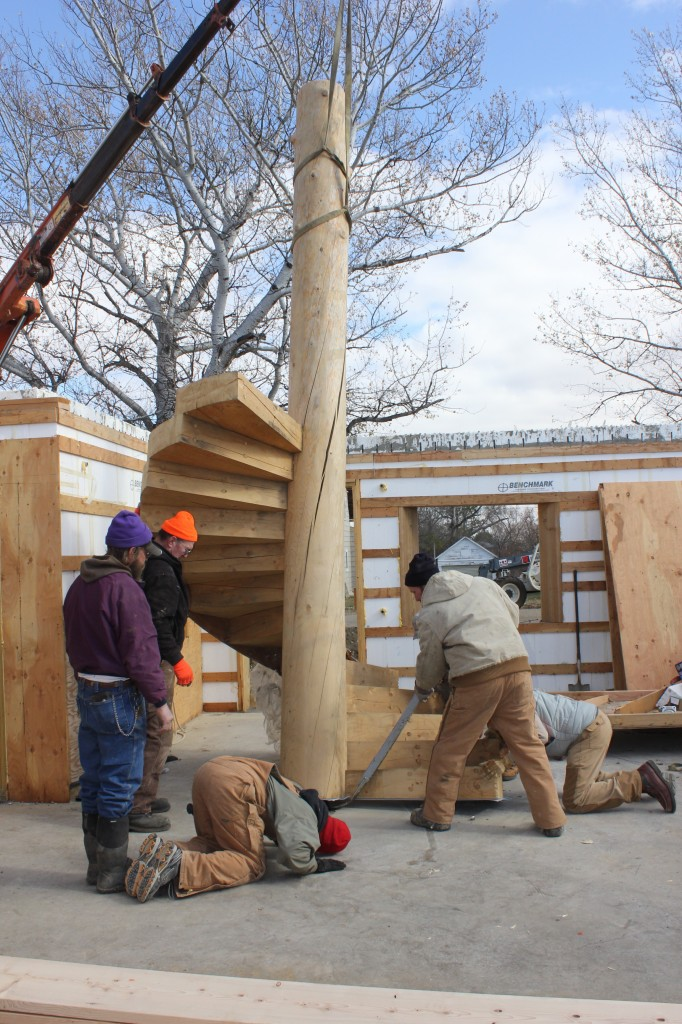 "A home being constructed by Ross Hansen (left rear) and Pfeifer & Son Construction in Faulkton will feature a number of unconventional designs and materials, such as this spiral staircase.  ""The tree it's cut from was a spruce that was 70 feet tall and was downed in 2007 by fire kill,"" Hansen said in October 2012, when they were working on this staircase. ""I milled it in 2008. It was about 80 years old… The center pole has a metal core base that goes into the floor, and each of the stairs was cut to be driven into the wood and held by epoxy."" Photo by Garrick Moritz/Faulk County Record"