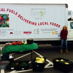Sarah Cooper stands in front of SPROUT MN'snewly converted 1997 Ford F350 bio-diesel truck at a farmers market held in an area hospital parking lot. Photo by Jessie Borkenhagen