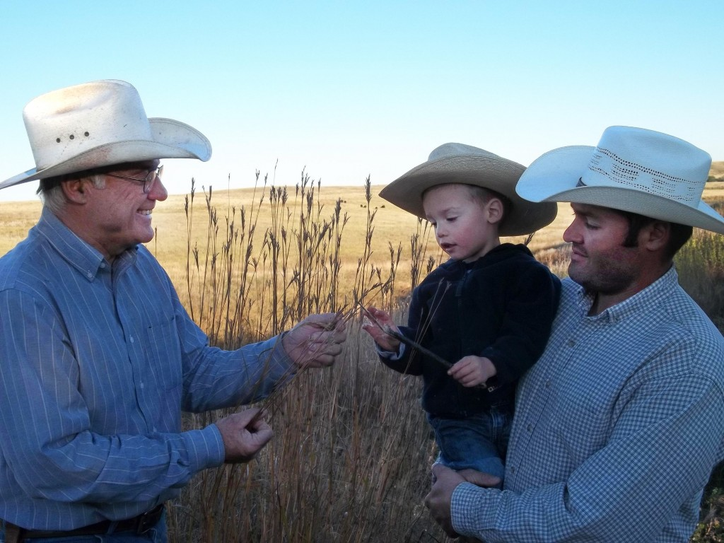 Much of the work at Rock Hills Ranch has been handed over to Lyle Perman's son, Luke Perman, pictured at right. He's holding a member of the next generation, Isaac, who's getting a lesson from his grandfather Lyle. Photo courtesy Rock Hills Ranch