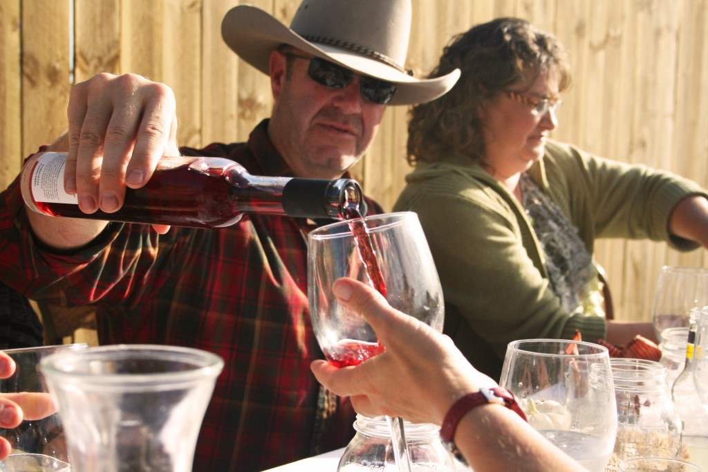 Tracy Brumfield pours some local wine for another diner at the harvest dinner held at The Field in Adrian, N.D. Photo by Heidi Marttila-Losure