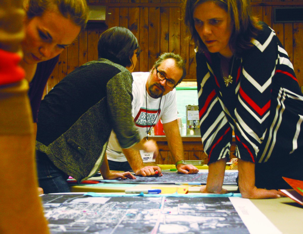 Landscape architect Matt Fridell listens to a Webster resident as participants of his group drew on large maps to give insight into where they like to spend time in Webster, compared to where visitors spend time.