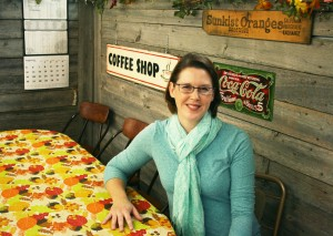 """The partition wall in the coffee area of Lake Grocery where Kristin Vandersnick is sitting was built by her husband, Matt. The Vandersnicks started married life in Sioux Falls, but """"We always knew we wanted to come back here,"""" she said. """"We wanted to live by grandmas and grandpas and have our kids have this small-town experience."""""""