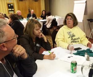 Scott Amundson and Marcia Erickson listen as Linda Salmonson tells a story of regional cooperation.