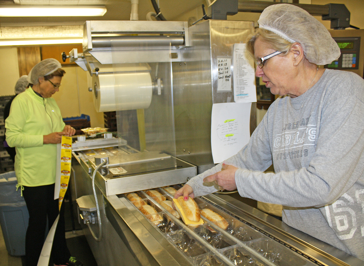 Marsha Bordewyk (left) and Cheryl Schryvers  (right) pack Dakota Tom's sandwiches sold at a  local church fundraiser. The business sells an average of 10,000 to 12,000 sandwiches each month at about 400 grocery and convenience stores across the country. The two women's husbands, Dick Bordewyk and Randy Schryvers, own the business with Dave VanRoekel. The three men were Corsica High School classmates.