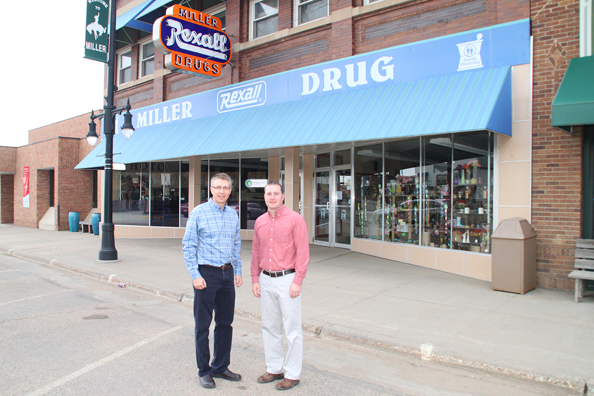 Pharmacists Trent Merkwan,  left, and Travis Anderberg stand outside  the Rexall Drug they jointly own in Miller, S.D.  The men began renovating second-story apartments after a 2013 housing study revealed the community had no available rentals. Photo by Deidra Schlechter