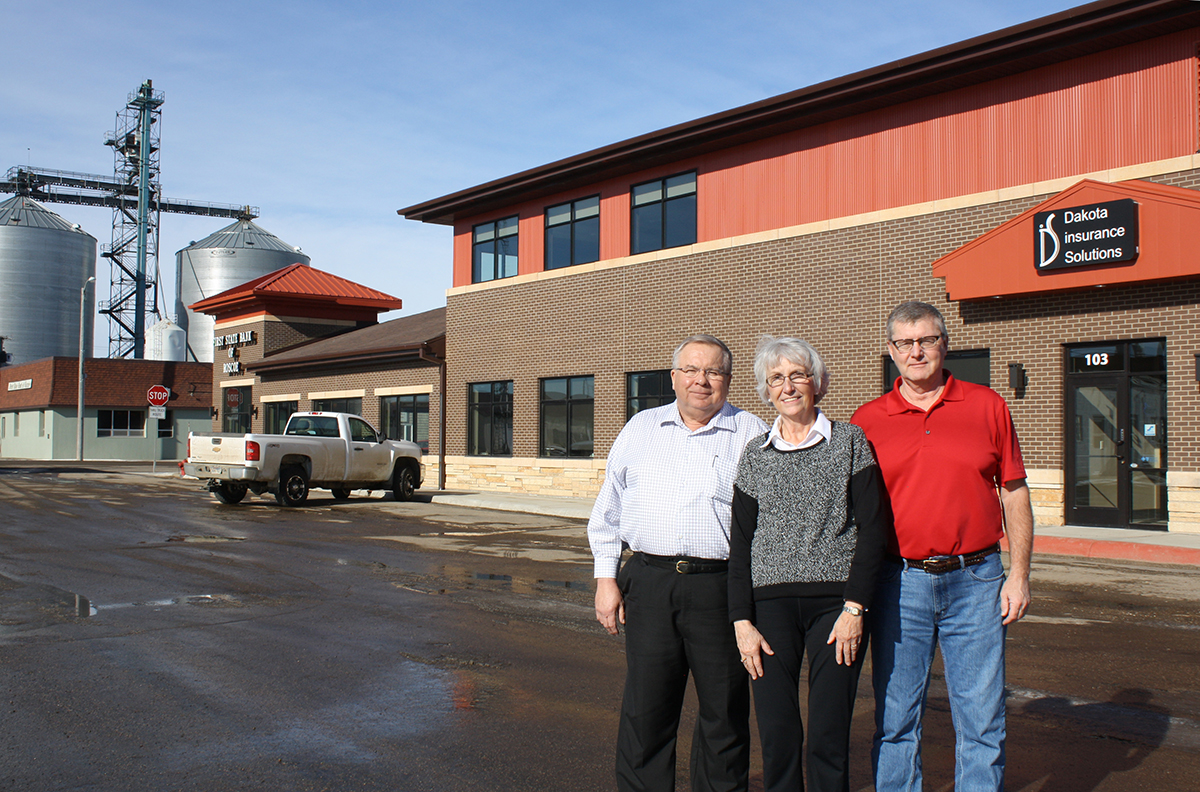 A strong ag sector has been the backbone of the success of businesses in Roscoe, according to, from left, John and Patty Beyers and Cliff Anderson. John Beyers owns First State Bank of Roscoe, which moved from the green building in the background to the new building across the street in December, just as he celebrated 50 years with the bank. Patty Beyers and Cliff Anderson co-own Dakota Insurance Solutions, which moved with the bank from the old location to the new.