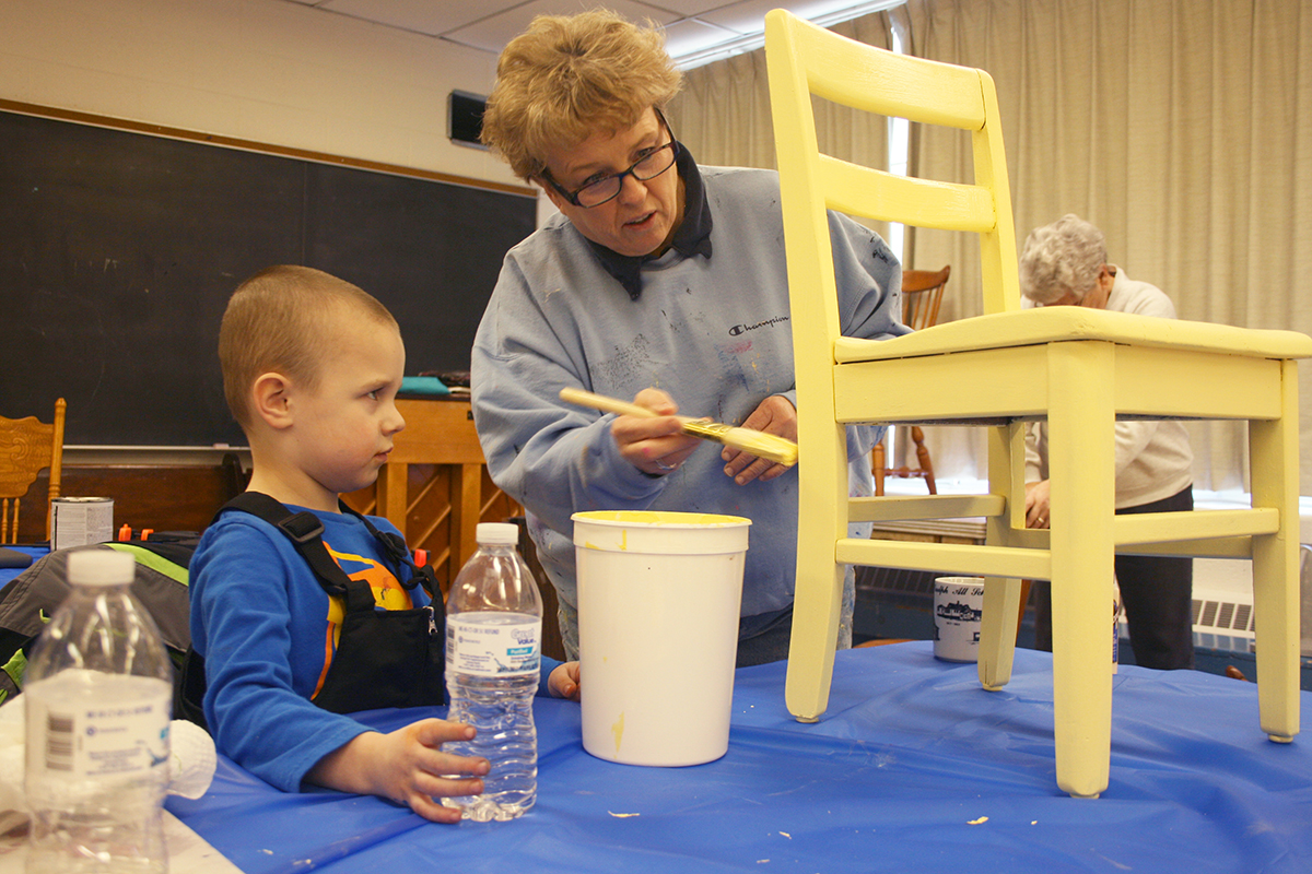 Local residents knew the roof had to be fixed. And then some local women had a brainstorm: They could use their talents in revitalizing furniture—something that several of them did as a hobby—to raise funds for the new roof. Here, Connie Finley and her grandson, Casyn, give an old chair new life with a bright new color.