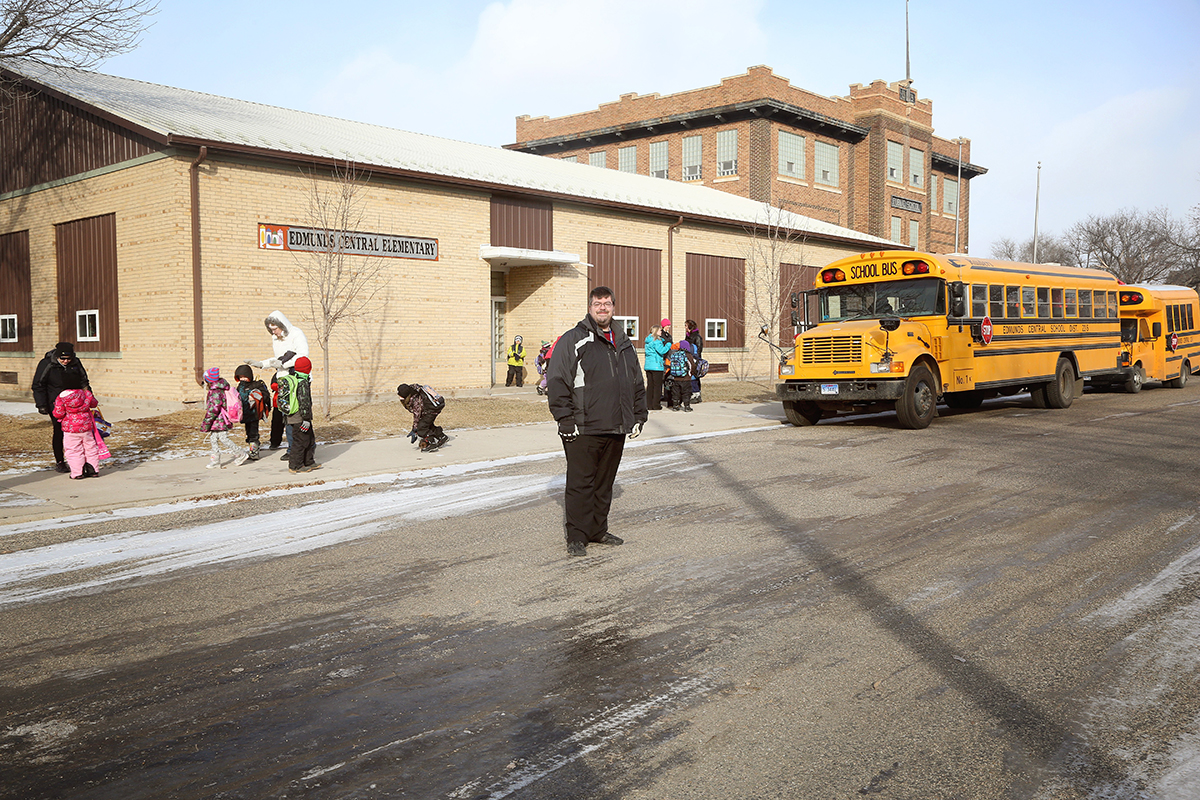 Superintendent Shawn Yates stands outside Edmunds Central Elementary at dismissal recently. In order to be proactive against possible future closure, the school district is discussing an $8.5 million building project that would include tearing down and replacing the two buildings in this photograph, which were built in 1952 (single-story elementary building) and 1919 (original, two-story schoolhouse) with new classroom space, a cafeteria and a competition-size gym. A 1965 building (not pictured) would remain. Photo by Sandra Beyers