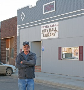 White Lake Mayor Jim Thiry stands in front of White Lake's shared city hall, public library and newspaper office on Main Street.