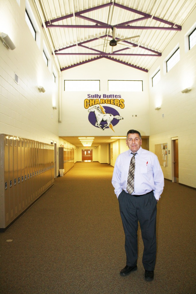 "Superintendent Kevin Pickner stands in the new commons area of Sully Buttes High School, which features ""clear story"" construction. Photo by Wendy Royston"