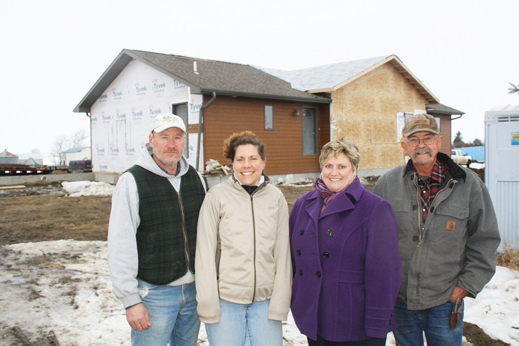 "Jamie and Jen Nye (left) and Shelley and Mayor Gary Wickersham (right), also known as NyeWick LLC, purchased the ""burnt house"" after it was damaged by fire and moved it to town. Photo by Wendy Royston"