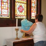 Carol White covers up the cross and candles on the altar of Trinity Episcopal Church in Groton, S.D. Photo by Groton Independent