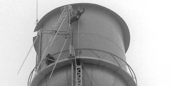 Workers scale Clark's water tower to work on antenna