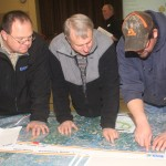 Monte Sippel, Bob Walter and TJ Harder look over the maps of the proposed route. Photo by Paul Kosel/Groton Daily Independent