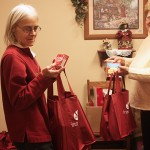 Frances Heeren, employee of the Interlakes Community Action Program thrift store, and Jeanie Fuller, ICAP county director, fill Christmas bags to be distributed this week. Photo by Bill Krikac, Clark County Courier